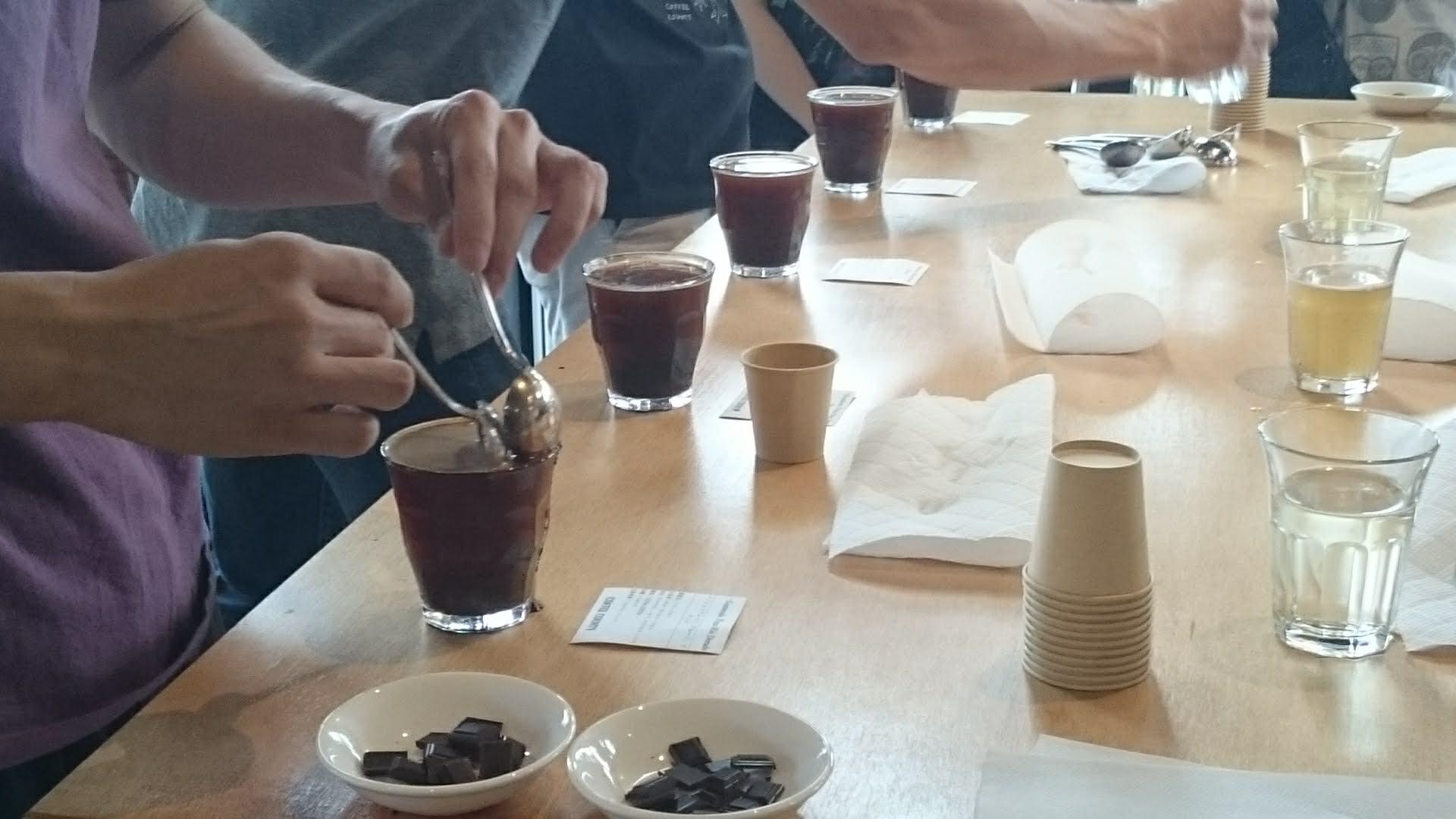 カッピング用コーヒーにお湯が注がれ上澄みと取る様子